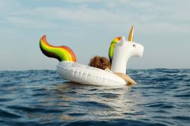 Ein Kind im Einhorn-Schwimmreifen auf dem Meer